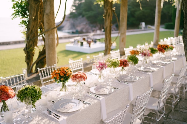 Hochzeitstafel empfang ein sehr langer tisch für gäste mit einer weißen tischdecke mit blumen