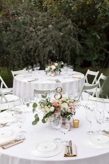 Hochzeitstafeleinstellung verziert mit frischen blumen in einem messingvase. hochzeitsfloristik. banketttisch für gäste im freien mit blick auf die grüne natur. blumenstrauß mit rosen-, eustoma- und eukalyptusblättern.