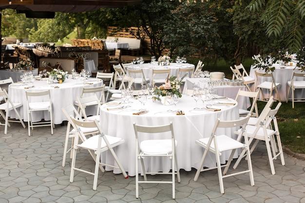 Hochzeitstafeleinstellung verziert mit frischen blumen in einem messingvase