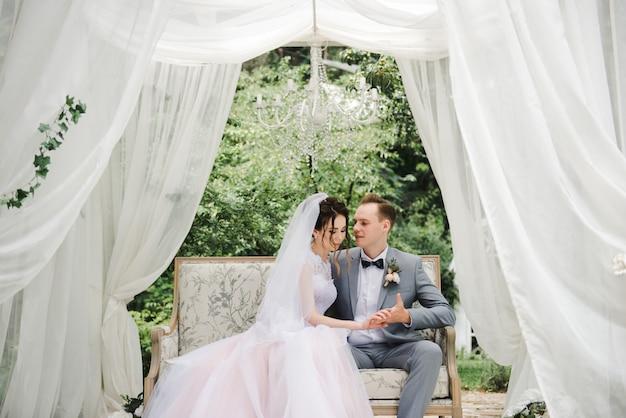 Hochzeitstag. die braut in einem rosa kleid, der bräutigam in einem grauen anzug.