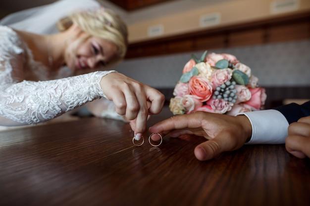 Hochzeitstag. hochzeit. zwei trauringe in den händen der jungvermählten hautnah. glückliche braut und bräutigam mit ihren eheringen