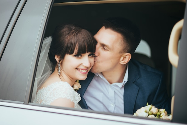 Hochzeitstag. hochzeitskuß, glücklicher und schöner bräutigam küsst die braut im hochzeitsauto