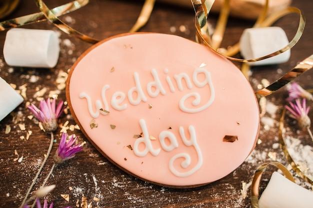 Hochzeitstag. süßigkeiten zur dekoration. handgemachter hochzeitsplätzchen verziert mit beschriftung auf holzoberflächennahaufnahme.
