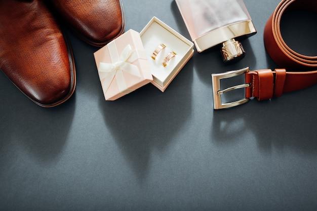 Hochzeitstagzubehör des bräutigams. braune lederschuhe, gürtel, parfüm, goldene ringe. männliche mode