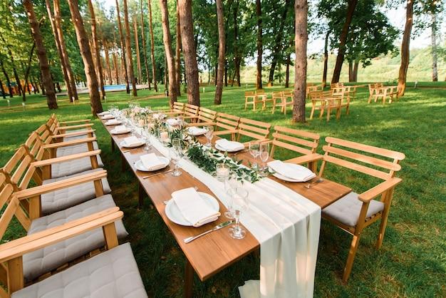 Hochzeitstisch mit rustikaler dekoration im wald. teller und grüner zweig mit kerzen auf dem tisch. grüne dekoration.