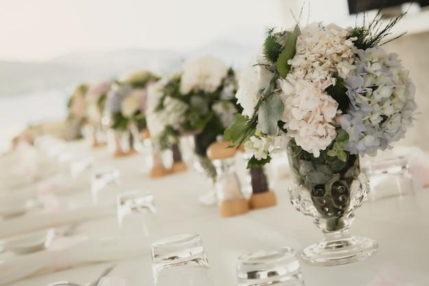Hochzeitstischdekoration an der frischen luft auf dem hintergrund des meeres. florale tischdekorationen für feiertage und abendessen. servieren für urlaub, event, party oder empfang in einem outdoor-restaurant. banner für website