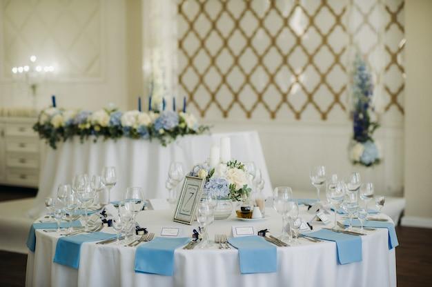 Hochzeitstischdekoration mit blauen blumen auf dem tisch im restaurant tischdekoration zum abendessen bei der hochzeit.