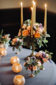 Hochzeitstischdekoration mit blumen auf dem tisch im schloss, tischdekoration zum abendessen bei kerzenschein. abendessen mit kerzen