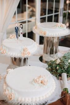 Hochzeitstorte mit lustigen figuren des bräutigams und der braut.