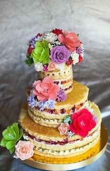 Hochzeitstorte. nackter handgemachter kuchen rustikal, mit rosen dekoriert.