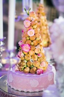 Hochzeitstorte verziert mit cremefarbenen blumen auf einem ständer.