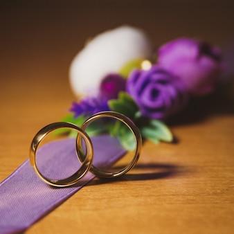 Hochzeitsverlobungsringe auf dem hintergrund einer dekorativen blumenstraußnahaufnahme