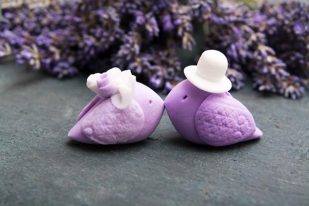 Hochzeitsvögel auf einem lavendelhintergrund. liebespaar auf einem fliederzeremoniekonzept