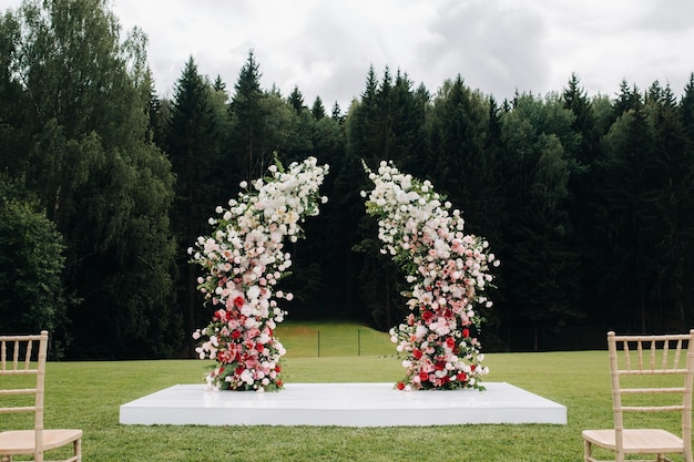 Hochzeitszeremonie auf der straße auf dem grünen rasen. dekor mit frischen blumenbögen für die zeremonie.