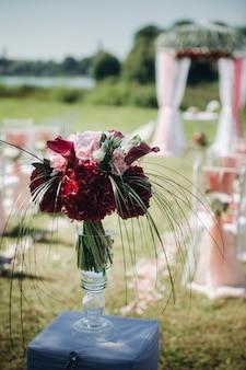 Hochzeitszeremonie auf der straße auf dem grünen rasendecor mit frischen blumenbögen für die zeremonie