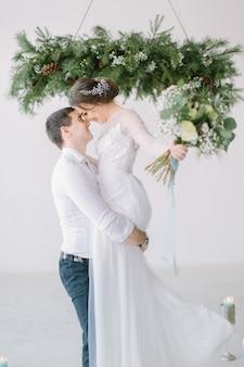 Hochzeitszeremonie in hellweißem raum mit kiefer, blumen und kerzen verziert