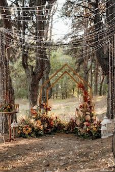 Hochzeitszeremonie mit getrockneten blumen auf einer wiese in einem kiefernwald