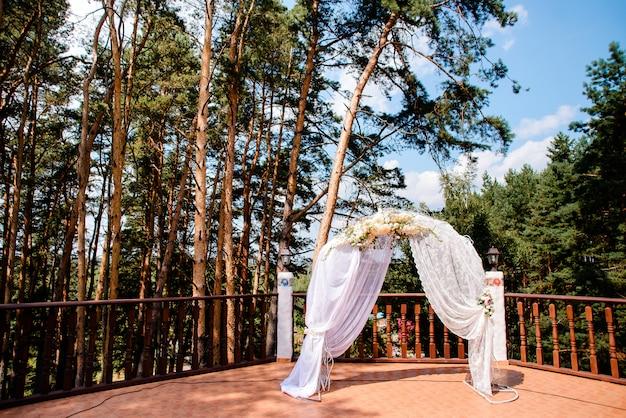 Hochzeitszeremoniebogen mit blumen und weißem stoff