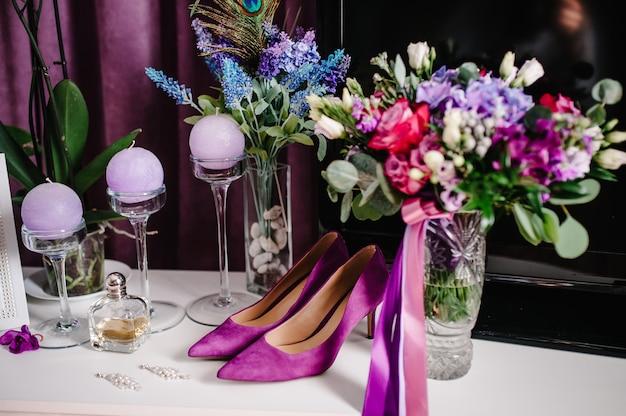 Hochzeitszubehör braut. stilvolle violette damenschuhe, ohrringe, blumen, kerzen und parfums auf dem tisch, der auf einem hölzernen hintergrundtisch steht.