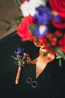 Hochzeitszubehör, brautblumenstrauß, eheringe auf einem holzstuhl.