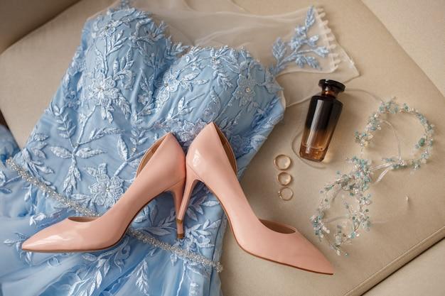 Hochzeitszubehör für die braut. rosa brautschuhe auf hohen absätzen auf blauem kleid in der nähe der parfümflasche und drei ringe: verlobungsring und eheringe für braut und bräutigam