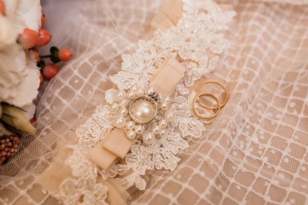 Hochzeitszubehör für eine braut und eheringe auf dem hochzeitskleid