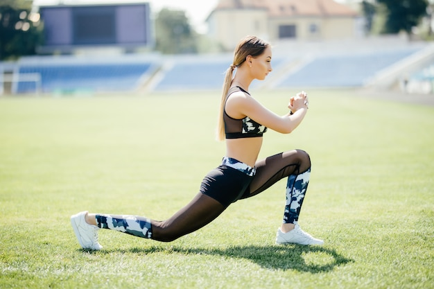 Hocken. junges schönheitsmädchen macht übungen im stadion