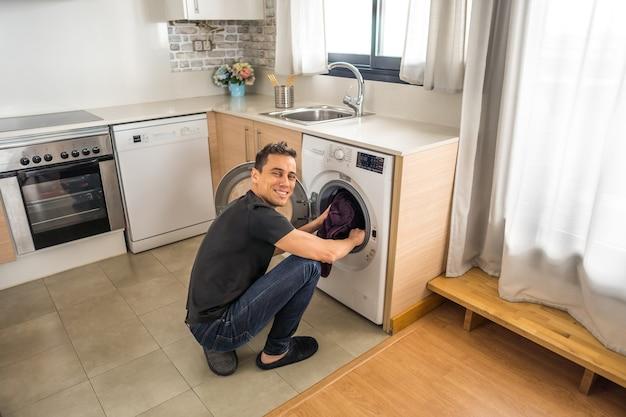 Hockender mann, der kleidung in die waschmaschine in der küche steckt. ganzkörper.