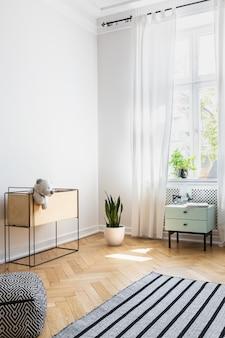 Hocker und gestreifter teppich im hellen wohnzimmer mit pflanzen und schrank unter dem fenster. echtes foto