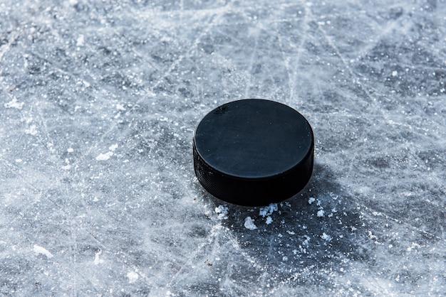 Hockey puck liegt auf der schnee nahaufnahme