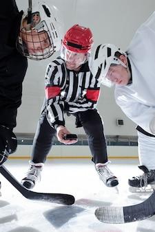 Hockey-schiedsrichter hält puck über eisbahn, während zwei rivalen mit stöcken darauf schauen, während sie sich darauf vorbereiten, ihn während des trainings zu schießen