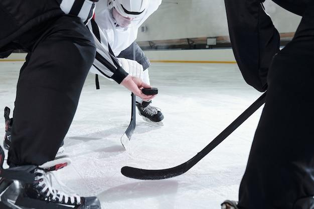 Hockey-schiedsrichter hält puck über eisbahn, während zwei rivalen mit stöcken sich nach vorne beugen und auf den moment warten, um der erste zu sein, um ihn zu schießen