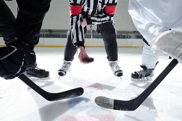 Hockey-schiedsrichter mit puck, der auf der eisbahn steht, mit zwei rivalen mit stöcken rechts und links, die auf den moment warten, um ihn zu schießen