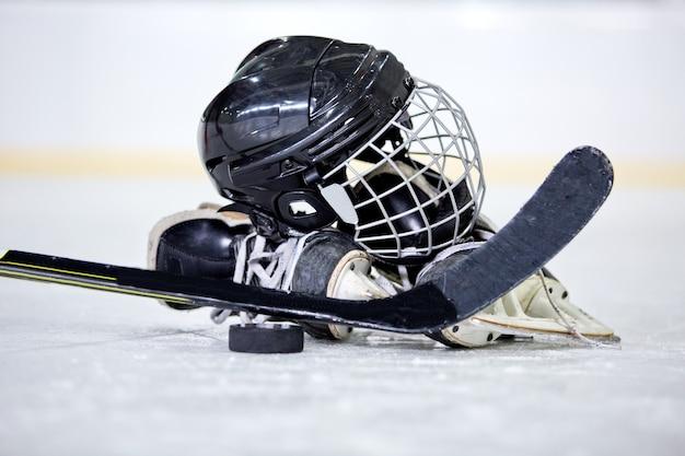 Hockeyhelm, puck, schläger und schlittschuhe auf der hockeybahn