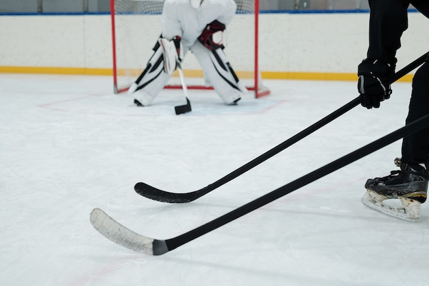 Hockeyschläger, die von zwei spielern in schlittschuhen, handschuhen und sportuniform gehalten werden, auf dem hintergrund des torhüters, der sich bereit macht, puck zu fangen?