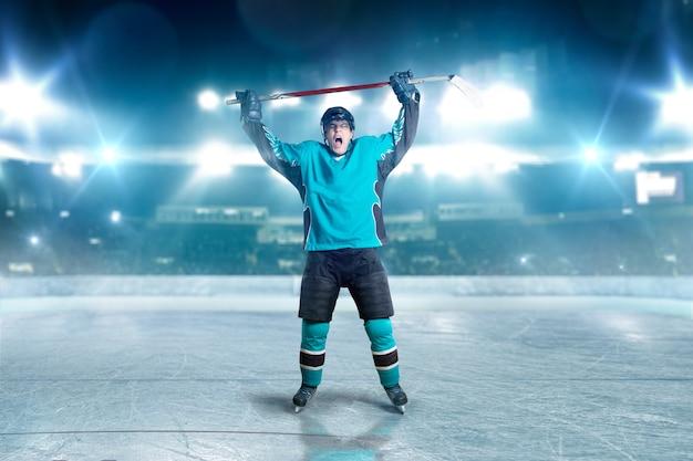 Hockeyspieler hob die hände, sieger warf den puck ins tor, scheinwerfer im hintergrund. männliche person mit helm, handschuhen und uniform in der eisarena