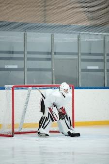 Hockeyspieler in weißer sportuniform, helm, handschuhen und schlittschuhen, die stock halten, während sie sich auf der eisbahn vor dem netz nach vorne beugen und auf den puck warten