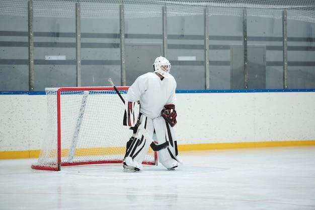 Hockeyspieler in weißer sportuniform, schutzhelm, handschuhe und schlittschuhe mit stock, während er auf der eisbahn vor dem netz steht und auf den puck wartet
