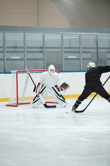 Hockeyspieler in weißer sportuniform, schutzhelm, handschuhen und schlittschuhen, der vor seinem rivalen auf der eisbahn steht und während des spiels puck schießen wird
