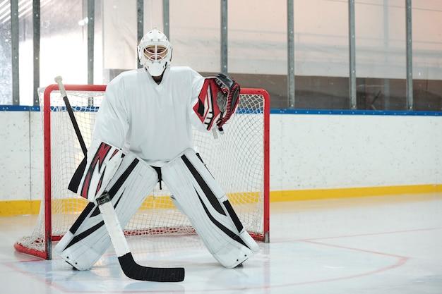 Hockeyspieler in weißer sportuniform, schutzhelm und handschuhen, die stock halten, während sie auf der eisbahn gegen das netz stehen und auf den puck warten