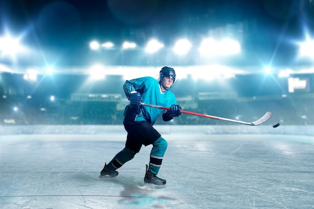 Hockeyspieler mit stock und puck macht einen wurf, eisarena, scheinwerfer im hintergrund. männliche person in helm, handschuhen und uniform, die spiel spielt