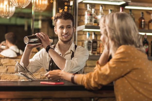 Höfliches gespräch. angenehmer junger barmann, der einen cocktail macht und seine kundin anlächelt, während sie mit ihm spricht