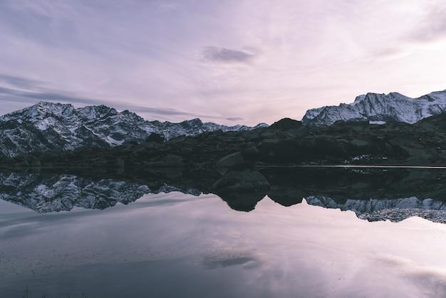 Höhenalpiner see in idyllischer landschaft. reflexion des schnee mit einer kappe bedeckten gebirgszugs bei sonnenuntergang.