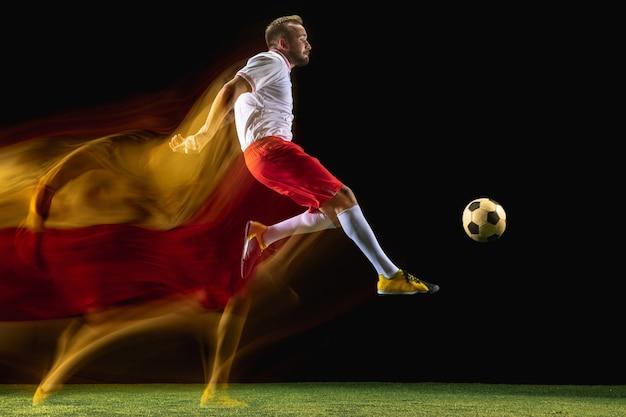 Höher. junger kaukasischer männlicher fußball- oder fußballspieler in sportbekleidung