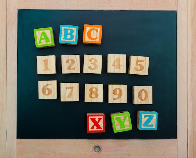 Hölzerne alphabetblöcke mit buchstaben und zahlen auf hölzernem brett
