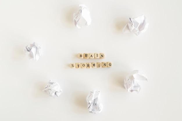 Hölzerne brainstorming blöcke, umgeben von zerknitterten papieren