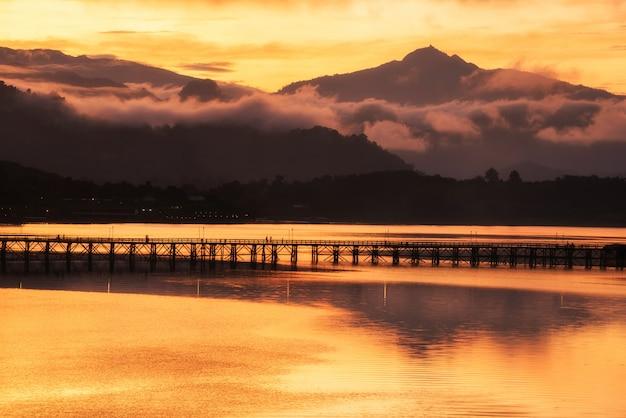 Hölzerne brücke des schattenbildes montag bei sonnenaufgang, sangkhlaburi