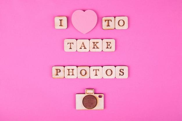Hölzerne buchstaben, aufschrift auf einem hellen rosa hintergrund. internationaler tag der fotografie