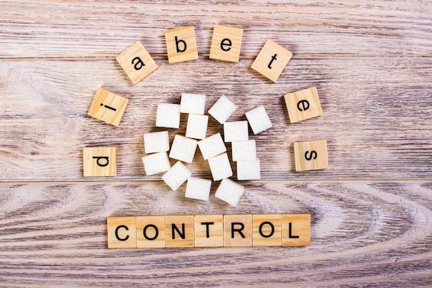 Hölzerne buchstaben des diabetes-kontrollblocks mit raffiniertem zucker