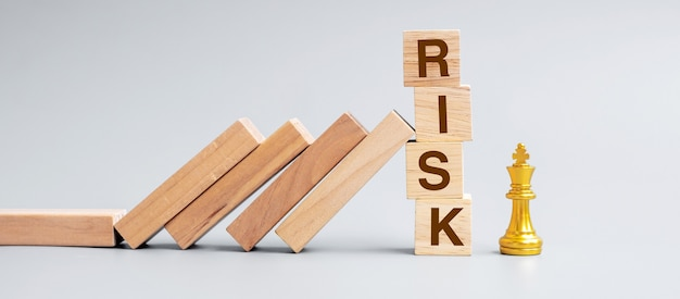 Hölzerne dominosteine, die gegen risiko-blöcke zu goldener schachkönigsfigur fallen. krise, finanzen, wirtschaftsrückgang, versicherung und konzept